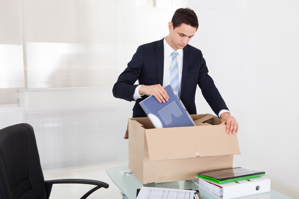 Employee packing files in cardboard box at desk in office
